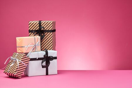 Different sizes, striped and plain, brown, rose and white paper gift boxes tied with colorful ribbons and bows on a pink surface and background. Concept of holidays, fests, celebrations, congratulations, presents, decorations, greetings. Close-up shot. Copy space.