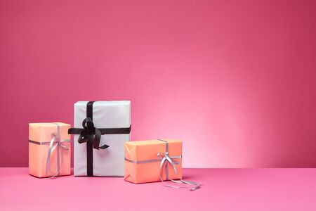 Different sizes, striped and plain, rose and white paper present boxes tied with colored ribbons and bows on a pink table and background. Concept of holidays, fests, celebrations, congratulations, presents, decorations, greetings. Close-up shot. Copy space.