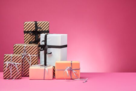 Different sizes, colorful, striped and plain, brown, rose and white paper present boxes tied with black and silver ribbons and bows on a pink stand and background. Concept of holidays, fests, celebrations, congratulations, presents, decorations, greetings. Close-up shot. Copy space.