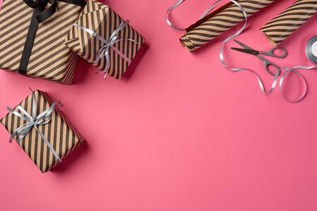 Different sizes, striped, brown present boxes tied with black and silver ribbons and bows on a pink background. Wrapping paper and metal scissors are laying nearby. Concept of holidays, fests, celebrations, congratulations, decorations, greetings. Close-up shot. Copy space. Top view. Stock fotó