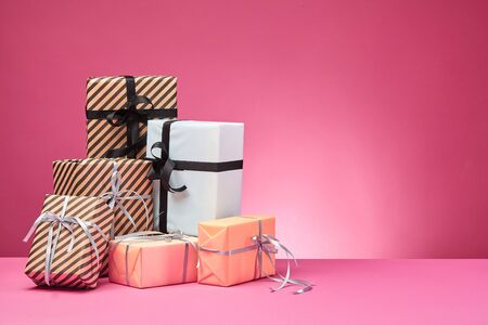 Different sizes, colorful, striped and plain, brown, rose and white paper present boxes tied with multicolored ribbons and bows on a pink surface and background. Concept of holidays, fests, celebrations, congratulations, presents, decorations, greetings. Close-up shot. Copy space. Stock fotó
