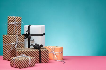 Different sizes, colorful, striped and plain, brown, pink and white paper gift boxes tied up with black and silver ribbons and bows on a pink surface and blue background. Concept of holidays, fests, celebrations, congratulations, presents, decorations, greetings. Close-up shot. Copy space.