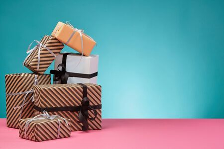 Various sized, striped and plain, brown, pink and white paper gift boxes tied with colorful ribbons and bows on a pink surface and blue background. Concept of holidays, fests, celebrations, congratulations, presents, decorations, greetings. Close-up shot. Copy space.