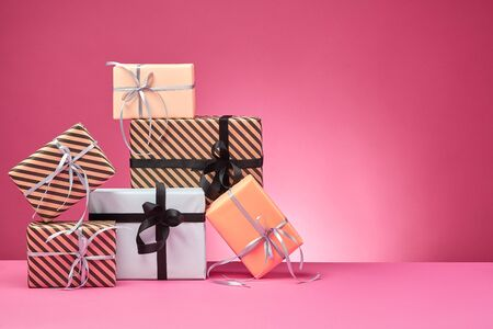 Various sized, striped and plain, brown, rose and white paper gift packages tied with black and silver ribbons and bows standing on a pink surface and background. Concept of holidays, fests, celebrations, congratulations, presents, decorations, greetings. Close-up shot. Copy space.