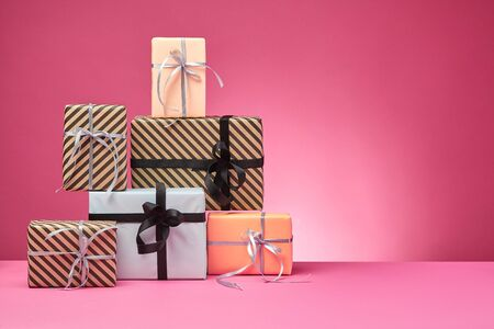 Various sized, striped and plain, brown, rose and white paper gift boxes tied with black and silver ribbons and bows standing on a pink surface and background. Concept of holidays, fests, celebrations, congratulations, presents, decorations, greetings. Close-up shot. Copy space.