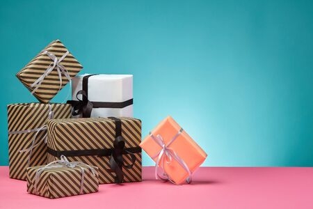 Various sized, colorful, striped and plain, brown, pink and white paper gift boxes tied with multicolored ribbons and bows on a pink surface and blue background. Concept of holidays, fests, celebrations, congratulations, presents, decorations, greetings. Close-up shot. Copy space.