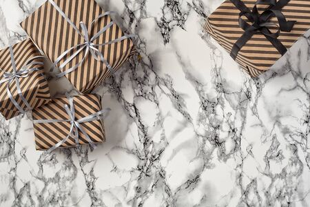 Different sizes, striped, brown, paper present packages tied with black and silver ribbons and bows on a marble background. Concept of holidays, fests, celebrations, congratulations, decorations, greetings. Close-up shot. Copy space. Top view. Stock fotó