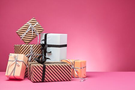 Different sizes, colorful, striped and plain, brown, rose and white paper gift boxes tied up with multicolored ribbons and bows on a pink surface and background. Concept of holidays, fests, celebrations, congratulations, presents, decorations, greetings. Close-up shot. Copy space.