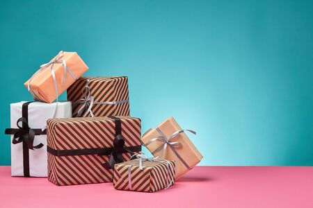 Various sized, colorful, striped and plain, brown, pink and white paper gift boxes tied with black and silver ribbons and bows on a pink surface and blue background. Concept of holidays, fests, celebrations, congratulations, presents, decorations, greetings. Close-up shot. Copy space.