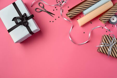 Different sizes, colorful, striped and plain, brown and white paper gift boxes tied with black and silver ribbons and bows on a pink background. Wrapping paper, decorative shiny stars and scissors are laying nearby. Concept of holidays, fests, celebrations, congratulations, presents, decorations, greetings. Close-up shot. Copy space. Top view.