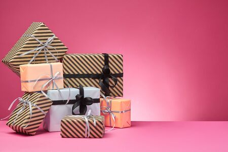 Different sizes, striped and plain, brown, rose and white paper gift boxes tied with colored ribbons and bows on a pink table and background. Concept of holidays, fests, celebrations, congratulations, presents, decorations, greetings. Close-up shot. Copy space.