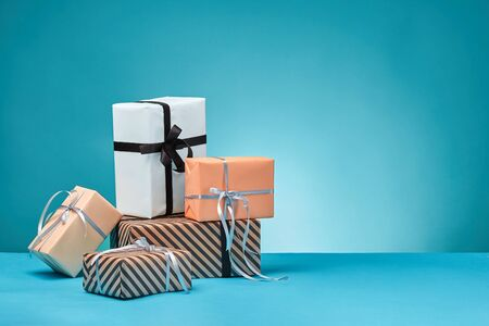 Different sizes, colorful, striped and plain, brown, pink and white paper gift boxes tied up with black and silver ribbons and bows on a blue surface and background. Concept of holidays, fests, celebrations, congratulations, presents, decorations, greetings. Close-up shot. Copy space.