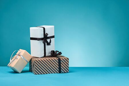 Different sizes, striped and plain, brown, pink and white paper gift boxes tied with black and silver ribbons and bows, standing on a blue stand and background. Concept of holidays, fests, celebrations, congratulations, presents, decorations, greetings. Close-up shot. Copy space.