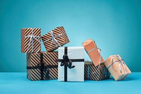 Different sizes, colorful, striped and plain, brown, pink and white paper present boxes tied with black and silver ribbons and bows on a blue stand and background. Concept of holidays, fests, celebrations, congratulations, gifts, decorations, greetings. Close-up shot. Copy space.