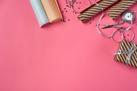 Striped brown present package tied with silver ribbon and bow on a pink background. Wrapping paper, decorative stars and scissors are laying nearby. Concept of holidays, fests, celebrations, congratulations, decorations, greetings. Close-up shot. Copy space. Top view. Stock fotó