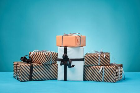 Different sizes, colorful, striped and plain, brown, pink and white paper gift boxes tied with black and silver ribbons and bows on a blue stand and background. Concept of holidays, fests, celebrations, congratulations, presents, decorations, greetings. Close-up shot. Copy space.