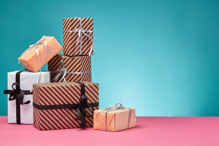 Various sized, colorful, striped and plain, brown, pink and white paper present boxes tied with black and silver ribbons and bows on a pink surface and blue background. Concept of holidays, fests, celebrations, congratulations, presents, decorations, greetings. Close-up shot. Copy space. Stock fotó