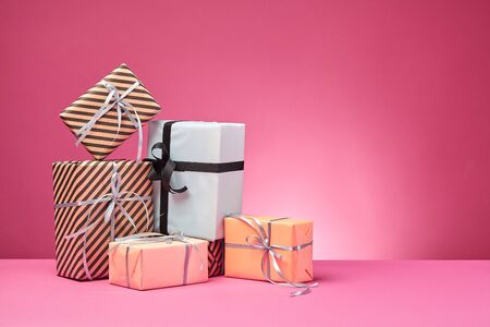 Different sizes, colorful, striped and plain, brown, rose and white paper present boxes tied with black and silver ribbons and bows on a pink surface and background. Concept of holidays, fests, celebrations, congratulations, presents, decorations, greetings. Close-up shot. Copy space. Stock fotó