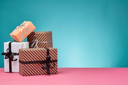 Different sizes, striped and plain, brown, pink and white paper gift packages tied with black and silver ribbons and bows standing on a pink surface and blue background. Concept of holidays, fests, celebrations, congratulations, presents, decorations, greetings. Close-up shot. Copy space.