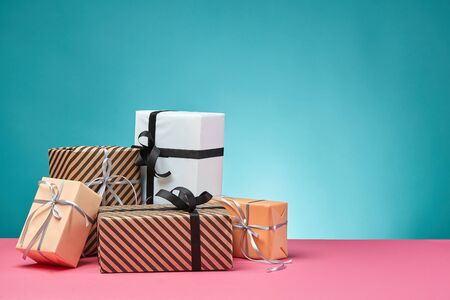 Different sizes, striped and plain, brown, pink and white paper gift boxes tied up with colorful ribbons and bows on a pink surface and blue background. Concept of holidays, fests, celebrations, congratulations, presents, decorations, greetings. Close-up shot. Copy space.