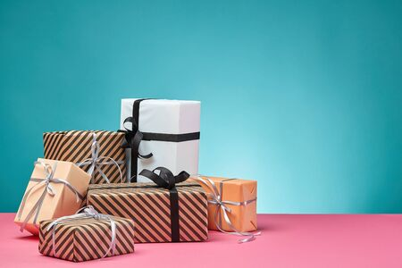 Different sizes, colorful, striped and plain, brown, pink and white paper present boxes tied up with black and silver ribbons and bows on a pink surface and blue background. Concept of holidays, fests, celebrations, congratulations, presents, decorations, greetings. Close-up shot. Copy space.