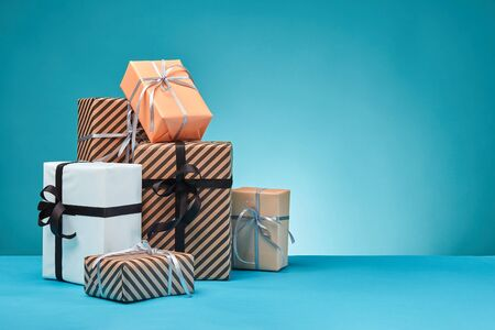 Different sizes, colorful, striped and plain, brown, pink and white paper present boxes tied up with black and silver ribbons and bows on a blue surface and background. Concept of holidays, fests, celebrations, congratulations, gifts, decorations, greetings. Close-up shot. Copy space.