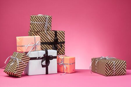 Different sizes, striped and plain, brown, rose and white paper gift boxes tied with colorful ribbons and bows on a pink stand and background. Concept of holidays, fests, celebrations, congratulations, presents, decorations, greetings. Close-up shot. Copy space. Stock fotó
