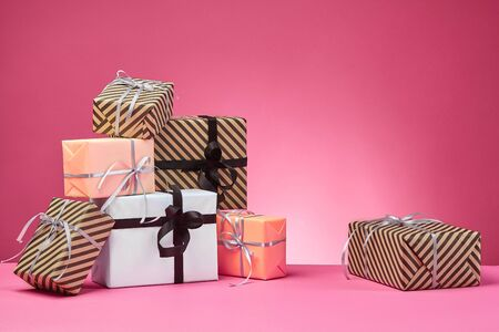 Different sizes, striped and plain, brown, rose and white paper gift boxes tied with multicolored ribbons and bows on a pink surface and background. Concept of holidays, fests, celebrations, congratulations, presents, decorations, greetings. Close-up shot. Copy space.