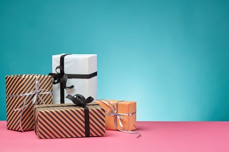 Various sized, striped and plain, brown, pink and white paper gift boxes tied with black and silver ribbons and bows standing on a pink surface and blue background. Concept of holidays, fests, celebrations, congratulations, presents, decorations, greetings. Close-up shot. Copy space.