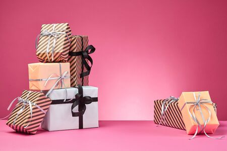Different sizes, striped and plain, brown, rose and white paper gift packages tied with colorful ribbons and bows on a pink surface and background. Concept of holidays, fests, celebrations, congratulations, presents, decorations, greetings. Close-up shot. Copy space. Stock fotó