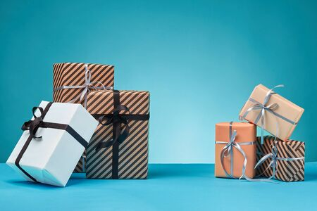 Different sizes, colorful, striped and plain, brown, pink and white paper gift boxes tied up with multicolored ribbons on a blue surface and background. Concept of holidays, fests, celebrations, congratulations, presents, decorations, greetings. Close-up shot. Copy space. Stock fotó