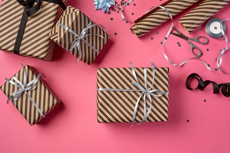 Different sizes, striped, brown present packages tied with black and silver ribbons and bows on a pink background. Wrapping paper and metal scissors are laying nearby. Concept of holidays, fests, celebrations, congratulations, decorations, greetings. Close-up shot. Copy space. Top view.