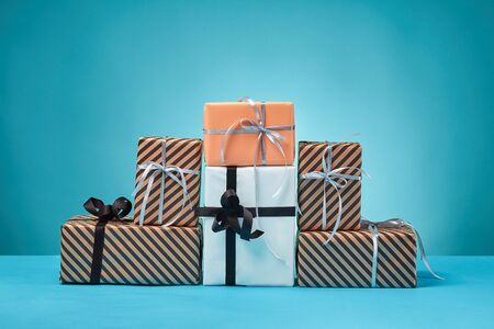 Different sizes, colorful, striped and plain, brown, pink and white paper gift boxes tied with multicolored ribbons on a blue table and background. Concept of holidays, fests, celebrations, congratulations, presents, decorations, greetings. Close-up shot. Copy space.