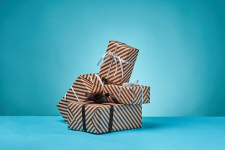 Different sizes, colorful, striped, brown paper gift boxes tied with black and silver ribbons and bows on a blue table and background. Concept of holidays, fests, celebrations, congratulations, presents, decorations, greetings. Close-up shot. Copy space. Stock fotó