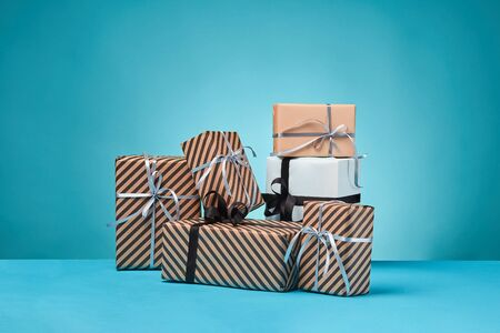 Various sized, colorful, striped and plain, brown, pink and white paper gift boxes tied with multicolored ribbons on a blue surface and background. Concept of holidays, fests, celebrations, congratulations, presents, decorations, greetings. Close-up shot. Copy space. Stock fotó