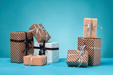 Different sizes, striped and plain, brown, pink and white paper gift boxes tied with black and silver ribbons and bows, standing on a blue surface and background. Concept of holidays, fests, celebrations, congratulations, presents, decorations, greetings. Close-up shot. Copy space.