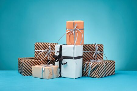 Different sizes, striped and plain, brown, pink and white paper gift boxes tied with colorful ribbons and bows on a blue table and background. Concept of holidays, fests, celebrations, congratulations, presents, decorations, greetings. Close-up shot. Copy space.