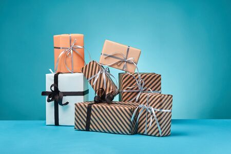 Various sized, striped and plain, brown, pink and white paper gift boxes tied with black and silver ribbons and bows, standing on a blue surface and background. Concept of holidays, fests, celebrations, congratulations, presents, decorations, greetings. Close-up shot. Copy space.
