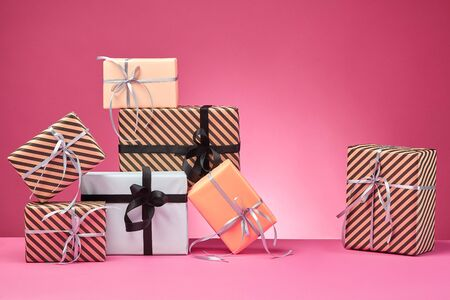 Various sized, striped and plain, brown, rose and white paper gifts tied with black and silver ribbons and bows standing on a pink stand and background. Concept of holidays, fests, celebrations, congratulations, presents, decorations, greetings. Close-up shot. Copy space. Stock fotó