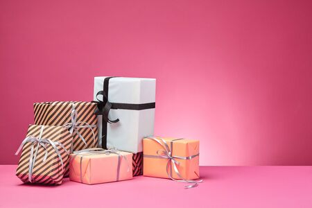 Different sizes, colorful, striped and plain, brown, rose and white paper present packages tied with black and silver ribbons and bows on a pink surface and background. Concept of holidays, fests, celebrations, congratulations, presents, decorations, greetings. Close-up shot. Copy space. Stock fotó