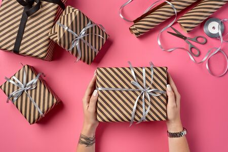 Hands of a woman with tattoos and watch are holding striped brown paper gift package tied with silver ribbon and bow on a pink background. Wrapping paper and metal scissors are laying nearby. Concept of holidays, fests, celebrations, congratulations, presents, decorations, greetings. Close-up shot. Copy space. Top view. Stock Photo
