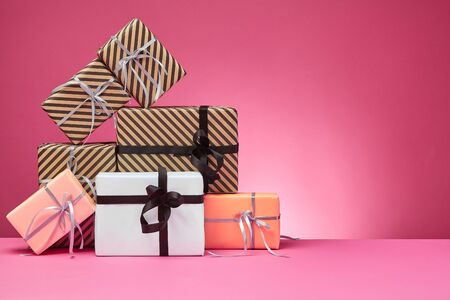 Different sized, colorful, striped and plain, brown, rose and white paper gift packages tied with colored ribbons and bows on a pink surface and background. Concept of holidays, fests, celebrations, congratulations, presents, decorations, greetings. Close-up shot. Copy space. Stock fotó