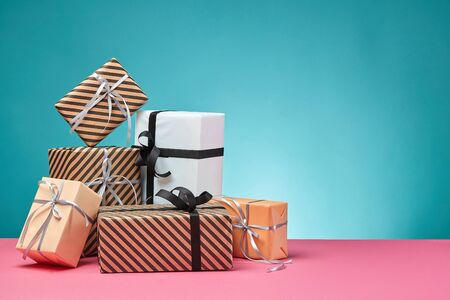 Different sizes, colorful, striped and plain, brown, pink and white paper gift boxes tied up with multicolored ribbons and bows on a pink surface and blue background. Concept of holidays, fests, celebrations, congratulations, presents, decorations, greetings. Close-up shot. Copy space.