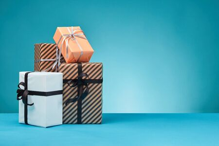 Different sizes, striped and plain, brown, pink and white paper gift boxes tied up with colorful ribbons and bows on a blue surface and background. Concept of holidays, fests, celebrations, congratulations, presents, decorations, greetings. Close-up shot. Copy space.