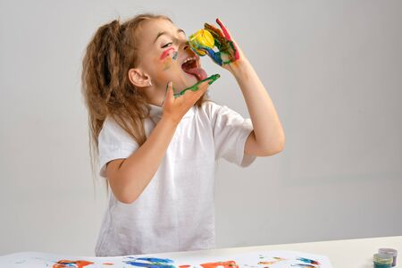 Little girl in white t-shirt sitting at table with  colorful paints