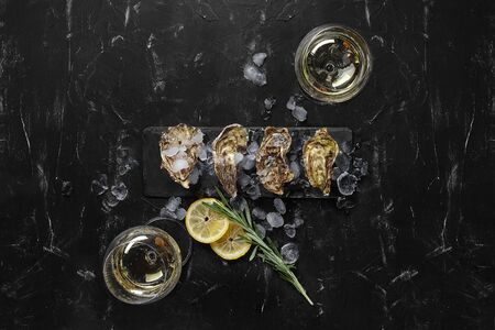Fresh delicious closed oysters, ice, lemon and a green twig of lavender on a rectangle slate and two glasses of champagne are on a black stone textured background. Meal at a restaurant. Healthy sea food. Top view with copy space. Close-up shot.