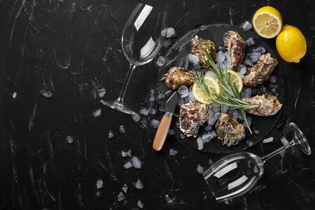 Fresh palatable closed oysters, ice, lemon and a green twig of lavender on a round slate, black stone textured background. Oyster knife and two empty glasses are laying nearby. Supper with champagne at a restaurant. Healthy sea food. Top view with copy space. Close-up shot.