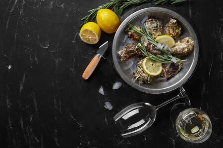 Fresh yummy closed oysters, ice, lemon and a green twig of lavender on a round metal plate and two glasses of white wine are on a black stone textured background. Oyster knife is laying nearby. Supper at a restaurant. Healthy sea food. Top view with copy space. Close-up shot.