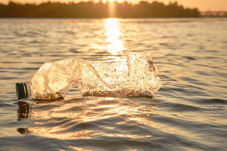 Old plastic bottle floats on the surface of the water. Sunset, green trees. People and ecology. Riverside pollution. Preservation of nature. Volunteering concept. Close-up shot.