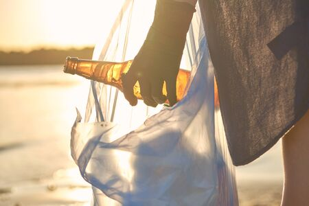 Young student in black gloves is walking with garbage bag along a dirty beach of the river and cleaning up sweepings, old glass bottles. People and ecology. Riverside pollution. Volunteer concept. Preservation of nature. Close-up shot. Banco de Imagens